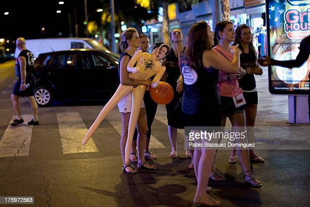A woman carries a sex doll in the street around the British Square on August 9 2013 in Benidorm Spain Benidorm is one of Europe's top package holiday...