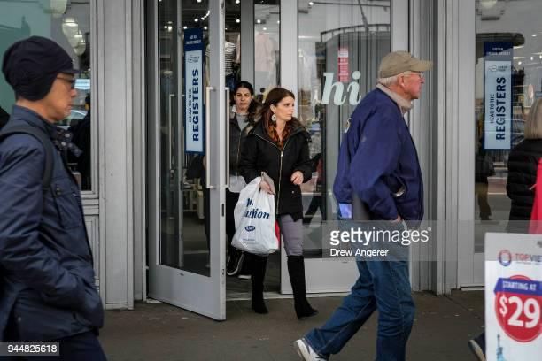 A woman carries a shopping bag as she exits an Old Navy store in the Herald Square neighborhood of Manhattan April 11 2018 in New York City US...
