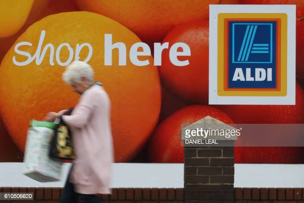 A woman carries a shopping bag as she walks past an Aldi supermarket store in London on September 26 2016 Aldi UK announced on Monday that it will...