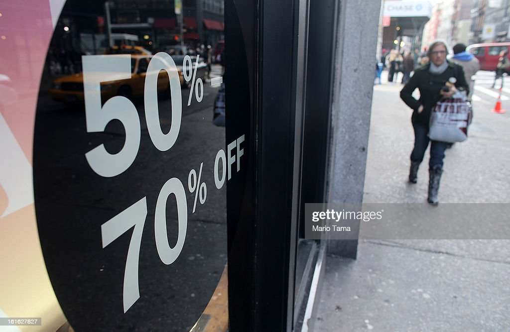 A woman carries a shopping bag past a store with a sale sign in the window in Manhattan on February 13, 2013 in New York City. The Commerce Department reported that retail sales were only up slightly in January following tax increases and high gas prices.