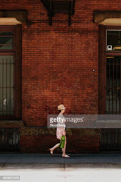 A woman carries a shopping bag while walking in the SoHo neighborhood of New York US on Wednesday June 18 2014 The Bloomberg Consumer Comfort Index a...