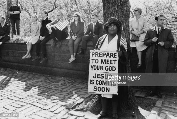 A woman carries a sign reading 'Prepare To Meet Your God Jesus Is Coming Soon' at a patriot parade in New York City 1967