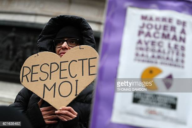 A woman carries a sign reading 'Respect Me' during a demonstration for equal pay between men and women on November 7 at Place de la Republique in...