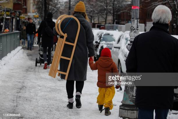 Woman carries a sledge as she crosses a bridge with a child at the Landwehr Canal in Berlin's Kreuzberg district on January 30, 2021.