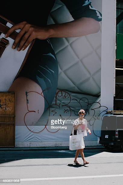 A woman carries a Steve Madden Ltd shopping bag while checking her mobile phone in the SoHo neighborhood of New York US on Wednesday June 18 2014 The...