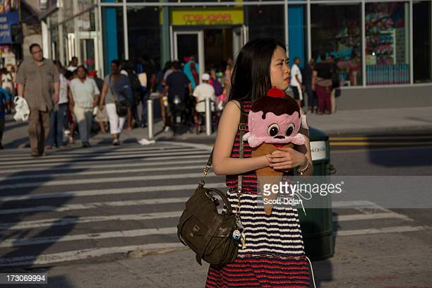 CONTENT] A woman carries a stuffed ice cream cone pillow across the street in this street photograph taken on Surf Avenue in Coney Island New York