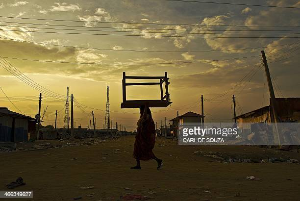 Woman carries a table on her head as she walks through almost deserted streets in Bor on February 1, 2014. Some Bor residents have begun to return to...