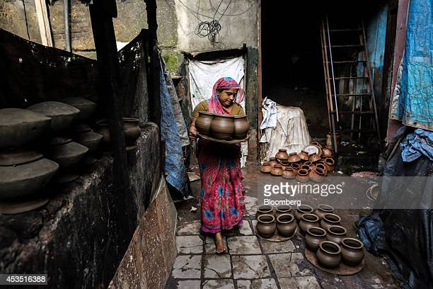 A woman carries a tray of clay pots at a pottery in the Dharavi slum area of Mumbai India on Tuesday Aug 12 2014 Almost a year after Reserve Bank of...