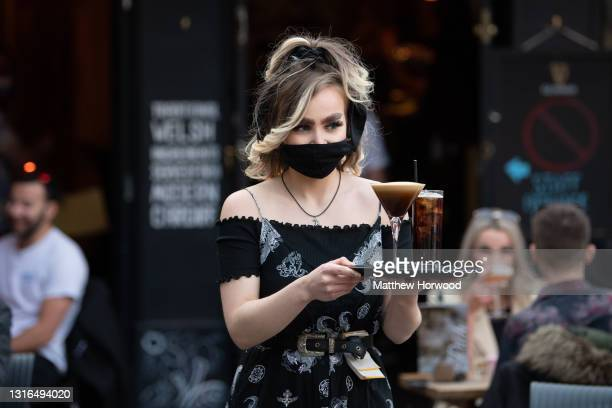Woman carries a tray of drinks at Pitch bar on April 26, 2021 in Cardiff, Wales. Outdoor hospitality reopens today in Wales and it is expected indoor...
