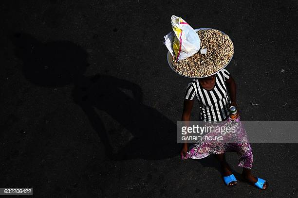 A woman carries a tray of peanuts on her head to sell in the streets of Libreville on January 20 during the 2017 Africa Cup of Nations football...