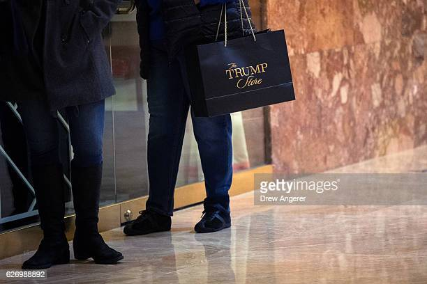 A woman carries a 'Trump' brand shopping bag at Trump Tower December 1 2016 in New York City Presidentelect Donald Trump and his transition team are...