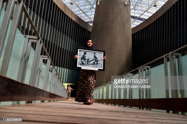 A woman carries a tsunami related picture during a photograph exhibition ahead of the 2004 Boxing Day tsunami anniversary in the tsunami museum...