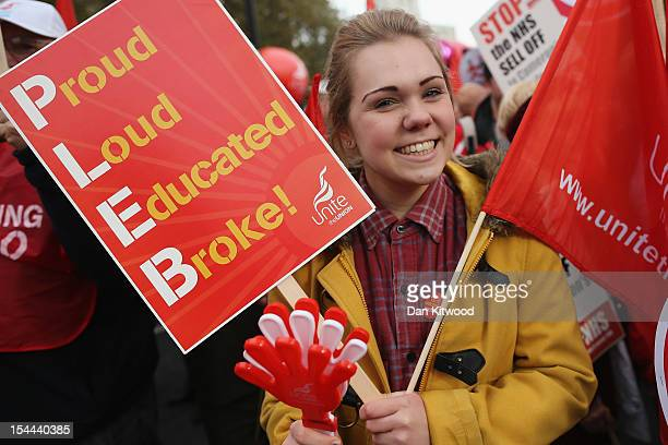 A woman carries a Unite trade union flag and placard with slogan spelling out the word 'PLEB Proud Loud Educated Broke' while taking part in a TUC...