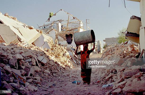 Woman carries a vessel to her tent through the rubble of Kadila, a village on the outskirts of Bhuj, India February 6, 2001 following an earthquake...