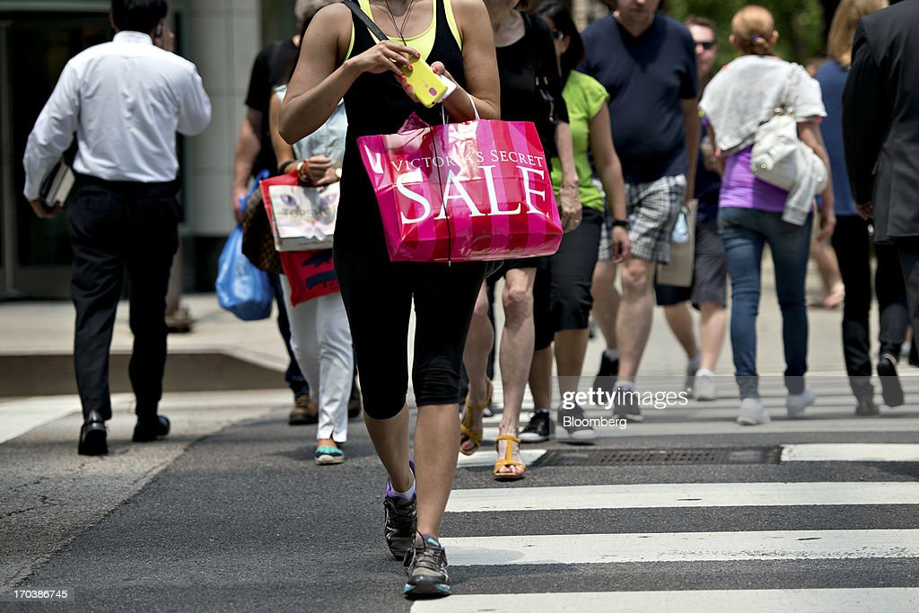 A woman carries a Victoria's Secret shopping bag as she walks through a retail area known as the 'Magnificent Mile' in Chicago, Illinois, U.S., on Tuesday, June 11, 2013. Sales at U.S. retailers probably rose in May as an improving job market gave consumers the confidence to shop for automobiles, home furnishings and clothing, economists said before reports this week. Photographer: Daniel Acker/Bloomberg via Getty Images