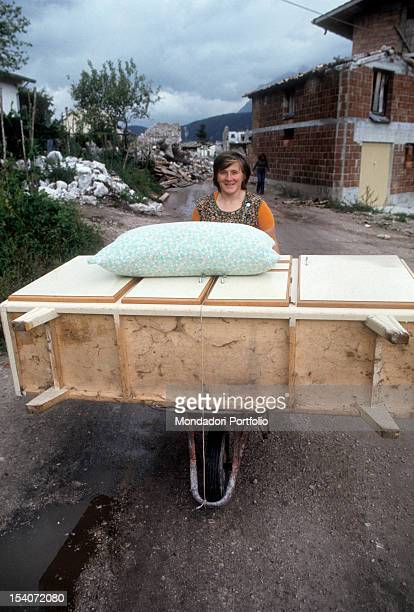 A woman carries a wardrobe into a wheelbarrow from the home destroyed by the earthquake FriuliVenezia Giulia May 1976
