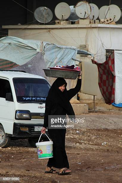 Woman carries a wash tub at the top of her head and a bucket in his hand at the tent city close to Al Salama border gate in Azez district of Aleppo,...
