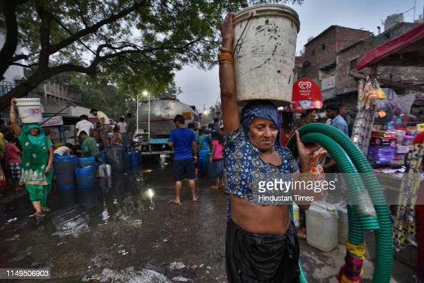 Woman carries a water container on her head after filling it from a Delhi Jal Board tanker, at Sanjay Colony in Okhla Phase II, on June 11, 2019 in...