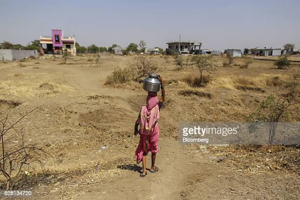 A woman carries a water container on her head filled from public drums at a village in Beed district Maharashtra India on Friday April 15 2016...