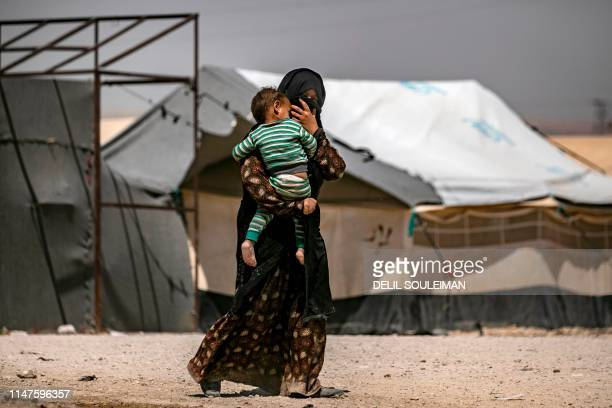 A woman carries a young child inside alHol camp for displaced people in alHasakeh governorate in northeastern Syria on June 02 2019 Kurdish...