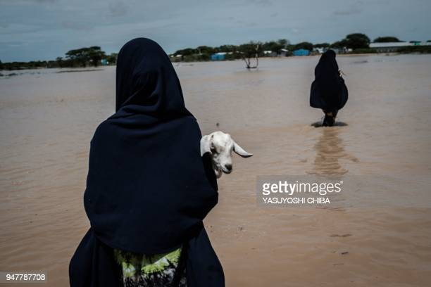Woman carries a young goat as she walks in floodwaters after a heavy rainy season downpour at the Dadaab refugee complex, in the north-east of Kenya,...