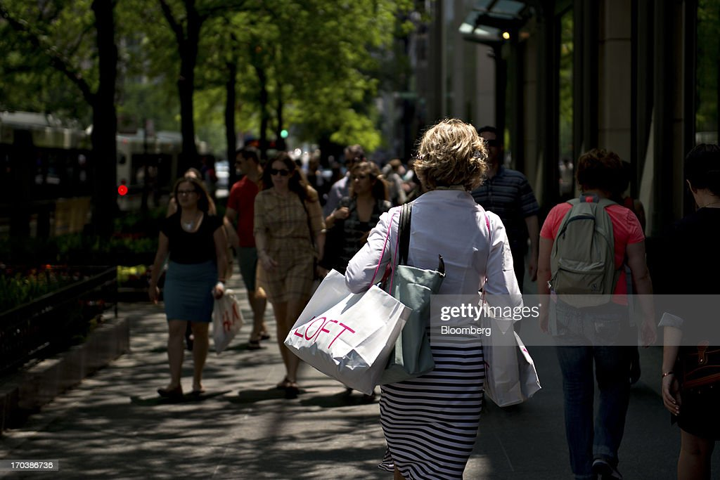 A woman carries an Ann Taylor Inc. Loft shopping bag as she walks through a retail area known as the 'Magnificent Mile' in Chicago, Illinois, U.S., on Tuesday, June 11, 2013. Sales at U.S. retailers probably rose in May as an improving job market gave consumers the confidence to shop for automobiles, home furnishings and clothing, economists said before reports this week. Photographer: Daniel Acker/Bloomberg via Getty Images