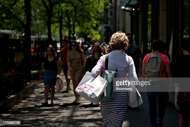 A woman carries an Ann Taylor Inc Loft shopping bag as she walks through a retail area known as the 'Magnificent Mile' in Chicago Illinois US on...