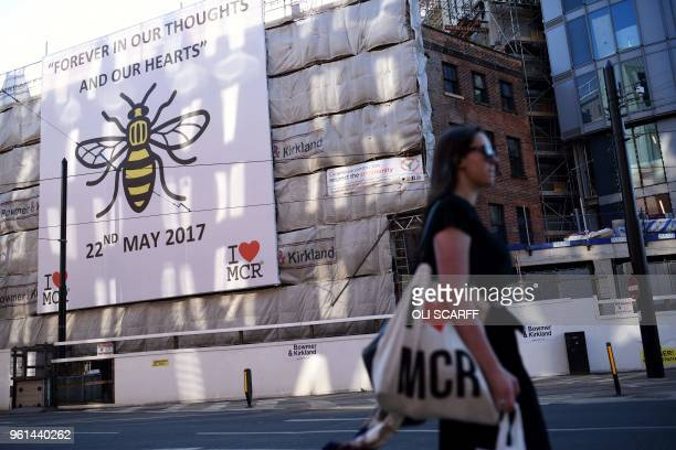 A woman carries an I Love MCR bag as she walks past a sign of support for Manchester set up in the wake of the Manchester Arena bombing in central...