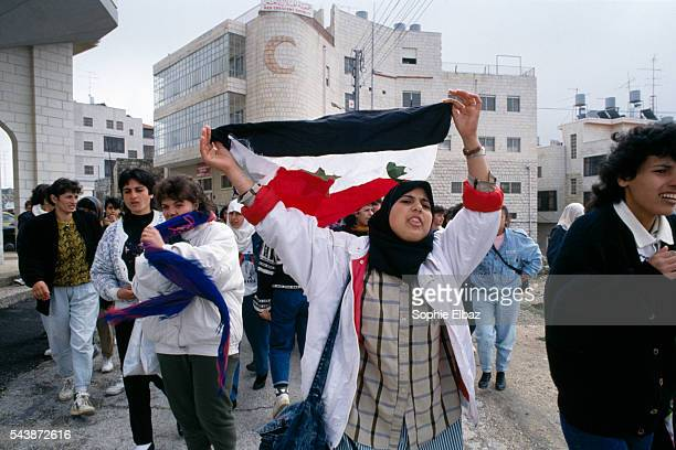 A woman carries an Iraqi flag during a Women's Day march as a reminder of daily injustices and in support of the Intifada The march lasted only 4...