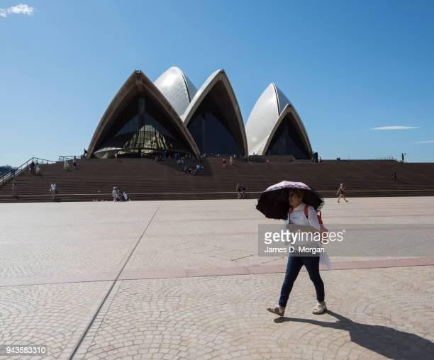 A woman carries an umbrella for shade in the afternoon heat as she crosses the forecourt of the Opera House on April 9 2018 in Sydney Australia...