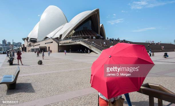 A woman carries an umbrella for shade in the afternoon heat next to the Opera House on April 9 2018 in Sydney Australia Sydney has been experiencing...