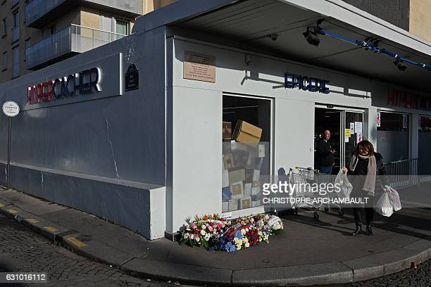 A woman carries bags as she walks past flowers laid at the site of the deadly attack against the Hyper Cacher supermarket following a ceremony...