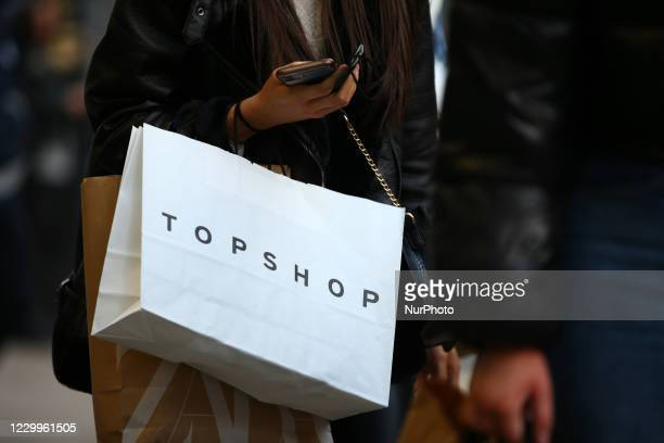 Woman carries bags from Arcadia-owned clothing retailer Topshop and from clothes chain Zara along Oxford Street in London, England, on December 5,...