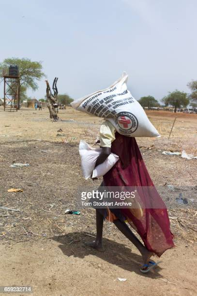 A woman carries bags home during an International Committee of the Red Cross distribution of seeds agricultural tools and food staples to households...