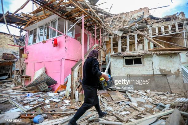 Woman carries belongings as she walks past a house damaged by recent shelling during a military conflict over the breakaway region of...