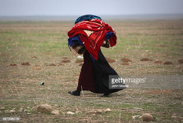A woman carries blankets into a Kurdishcontrolled area after fleeing her ISIL or Daeshheld frontline town on November 16 2015 to Sinjar Iraq...