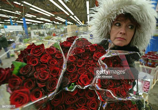 A woman carries bouquets of red roses in New Covent Garden Flower Market on February 11 2009 in London England New Covent Garden Flower Market is...