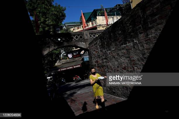 Woman carries bowls of soup past an alley in Hanoi on August 26, 2020.