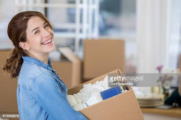 Woman carries box into her new home