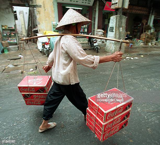 A woman carries boxes of Coca Cola cans along a Hanoi street to deliver them to a softdrink trader 07 October US Chamber President and CEO Thomas J...