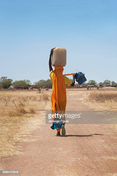 Woman carries bucket of water. South Sudan.