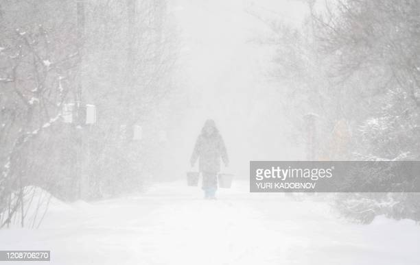Woman carries buckets of water from a well to her house in the village during a heavy snowfall outside Moscow on March 31, 2020. - The mayor of...