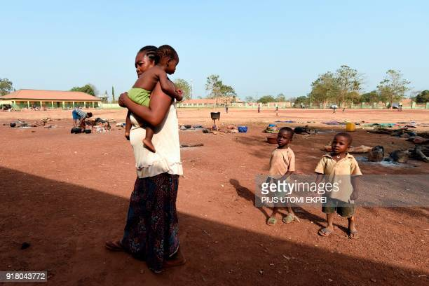 A woman carries child in her arms as she is followed by two children at the internally displaced people camp occupied largely by women and children...