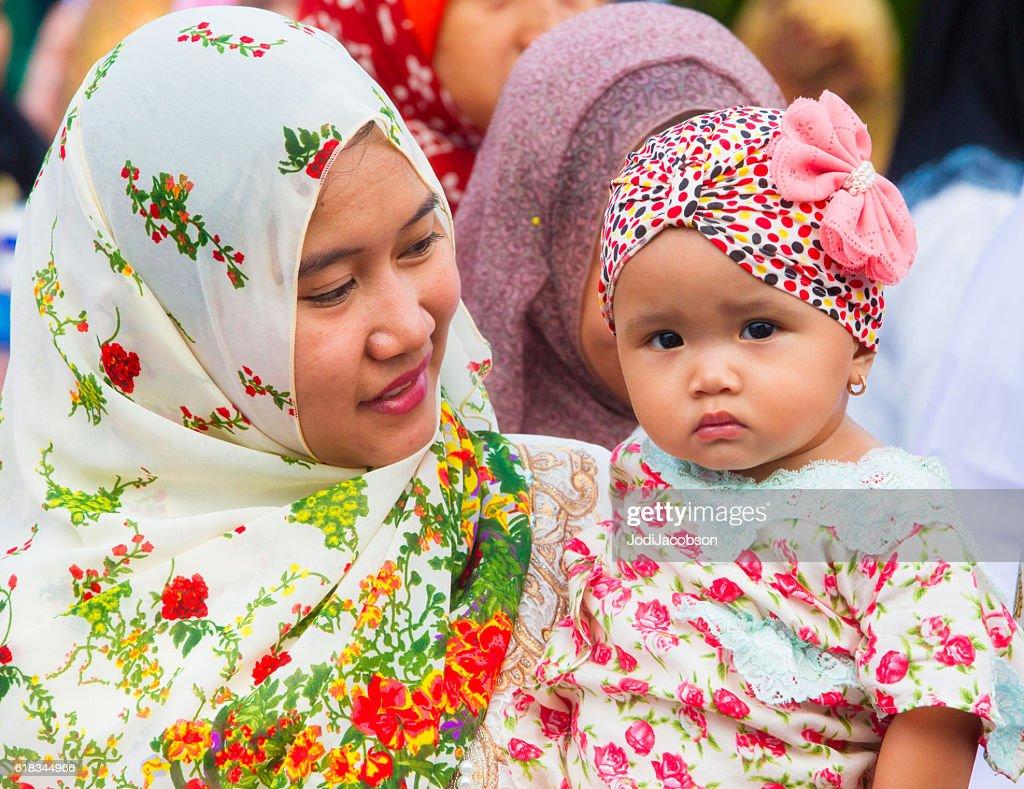 Woman carries child in Jakarta, Indonesia during Ramadan celebration. : Stock Photo