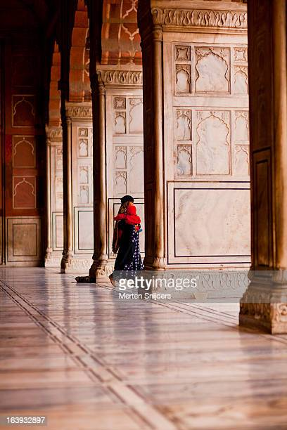 woman carries child in mosque - merten snijders stock pictures, royalty-free photos & images