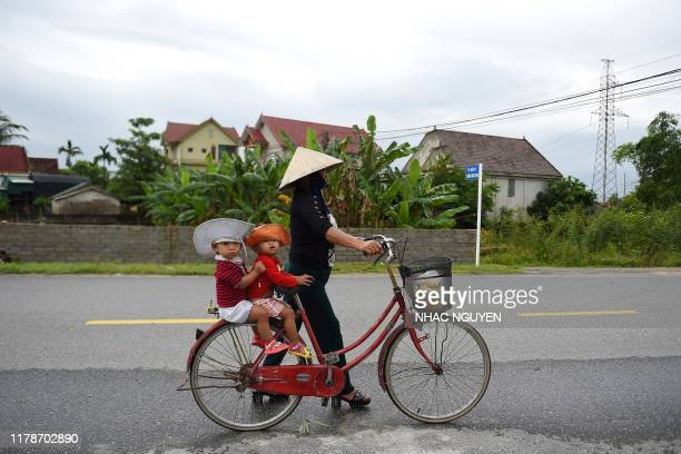 TOPSHOT A woman carries children on a bicycle in Nghe An province where families of missing Vietnamese migrants reside on October 29 2019 For up to...