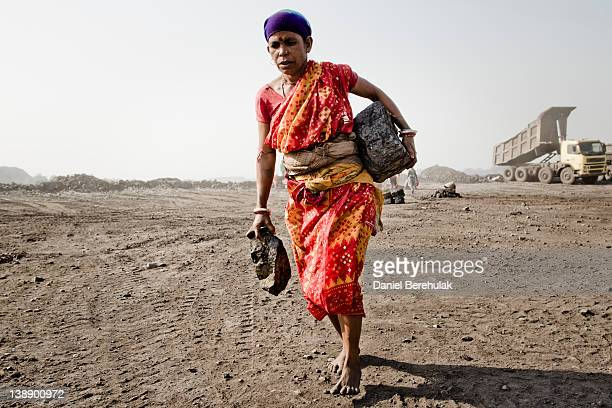 A woman carries chunks of coal as she walks past trucks arriving to dump refuse material at a dump site of an opencast coal mine in the village of...