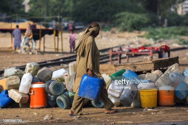 A woman carries containers filled with water in Karachi Pakistan on Saturday Dec 22 2018 Women and children walk miles each day in search...