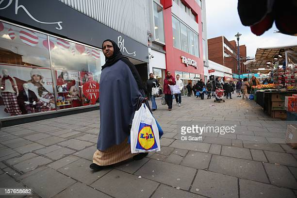 A woman carries discount supermarket shopping bags along Lewisham high street on December 5 2012 in London England The Chancellor of the Exchequer...