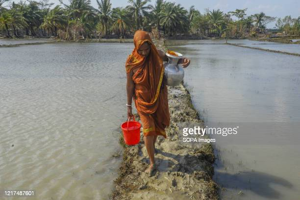 Woman carries drinking water in the aftermath of the extremely severe cyclonic storm Amphan. Thousands of shrimp enclosures have been washed away,...